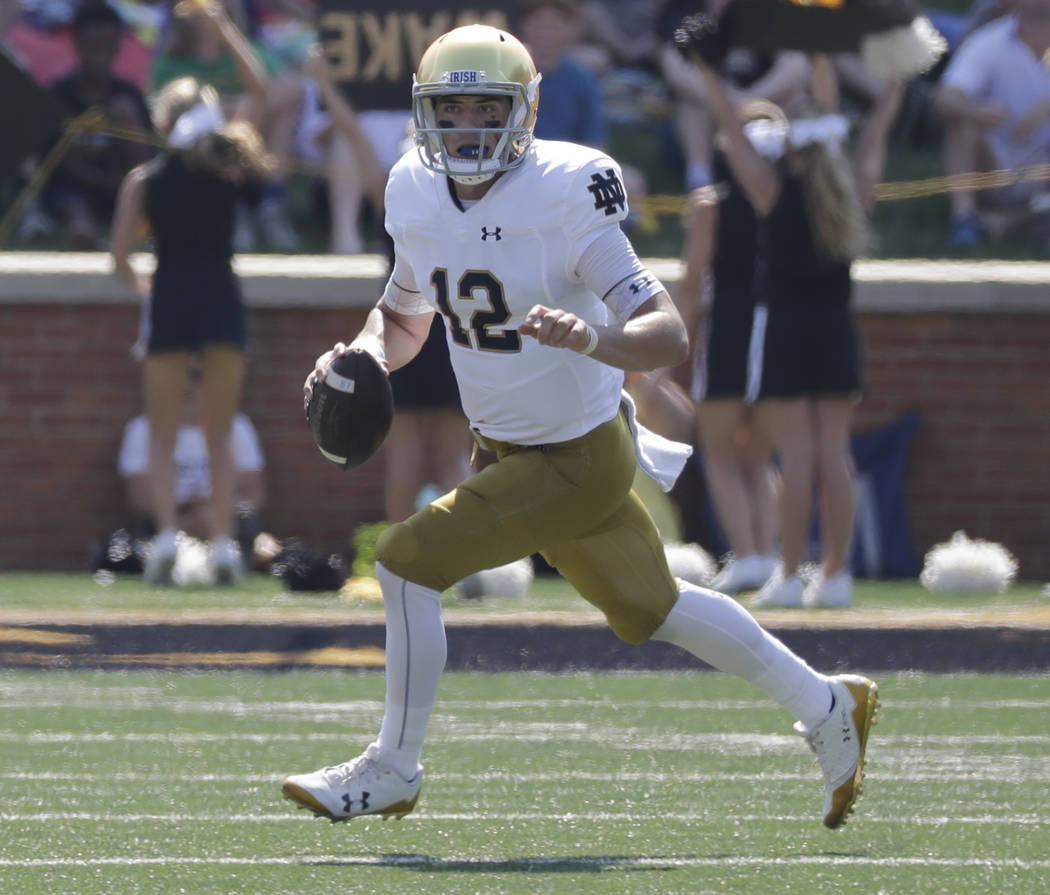 Notre Dame's Ian Book (12) rolls out against Wake Forest in the first half of an NCAA college football game in Winston-Salem, N.C., Saturday, Sept. 22, 2018. (AP Photo/Chuck Burton)