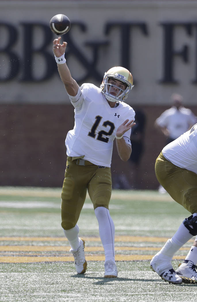 Notre Dame's Ian Book (12) throws a pass against Wake Forest in the first half of an NCAA college football game in Winston-Salem, N.C., Saturday, Sept. 22, 2018. (AP Photo/Chuck Burton)