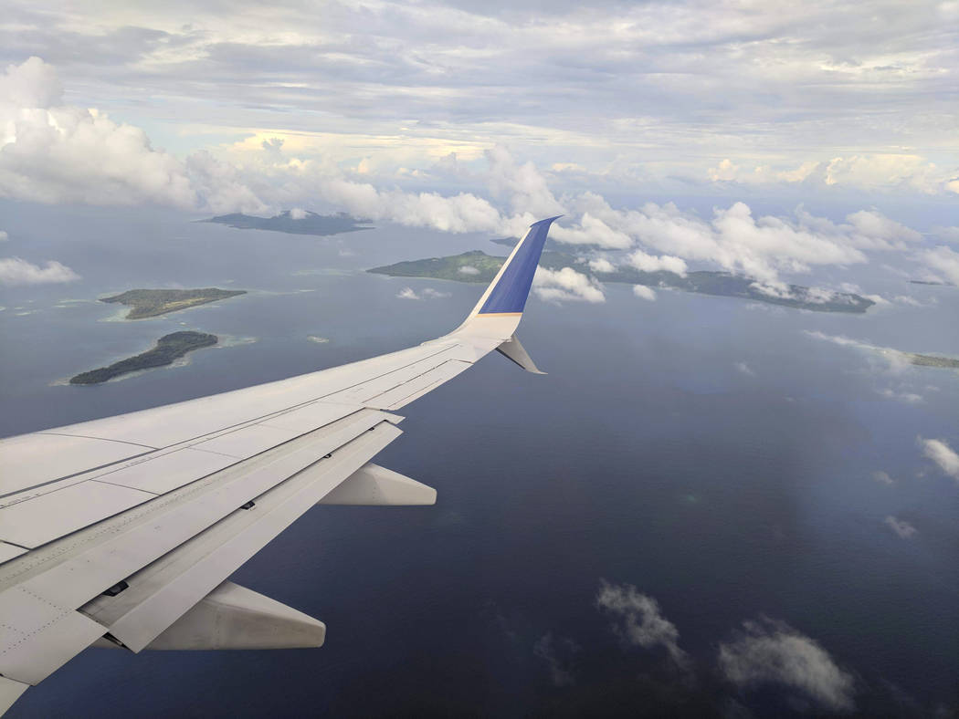 This Oct. 28, 2017, photo shows the right wing and winglet of a United Airlines 737-800ER airplane descending through a layer of clouds over the Chuuk Lagoon en route to Chuuk Airport in Weno, Fed ...