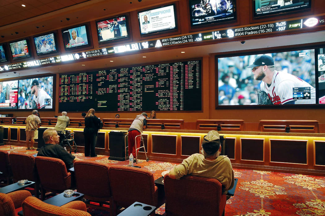 In this May 14, 2018, file photo, people make bets in the sports book at the South Point hotel and casino in Las Vegas. (AP Photo/John Locher, File)