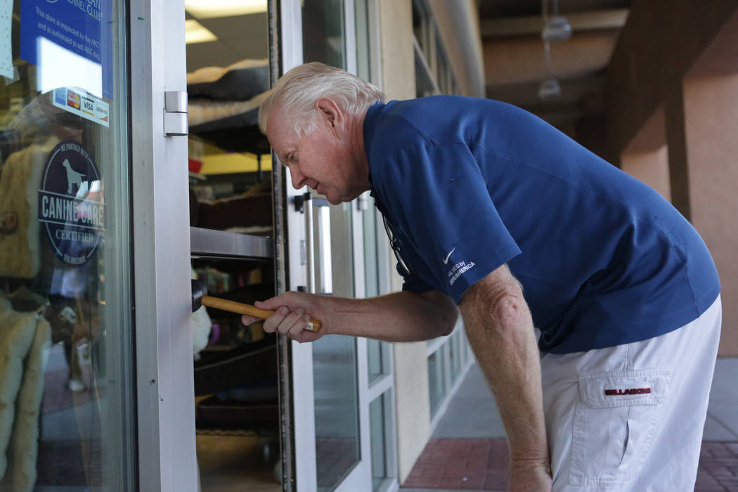Petland store owner Jeff Fausett clears away broken glass fragments from the door of his Las Vegas pet store after a break in and theft of two puppies on Friday, Sept. 28, 2018. (Michael Quine/Las ...