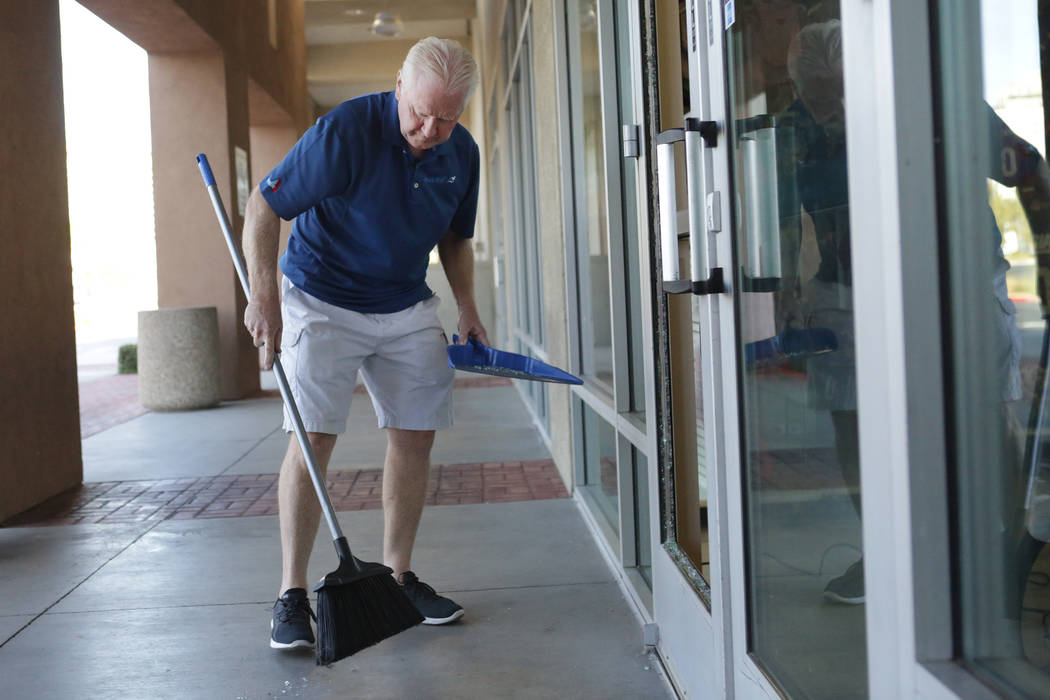 Petland store owner Jeff Fausett sweeps up broken glass from the door of his Las Vegas pet store after a break-in and theft of two puppies on Friday, Sept. 28, 2018. (Michael Quine/Las Vegas Revie ...