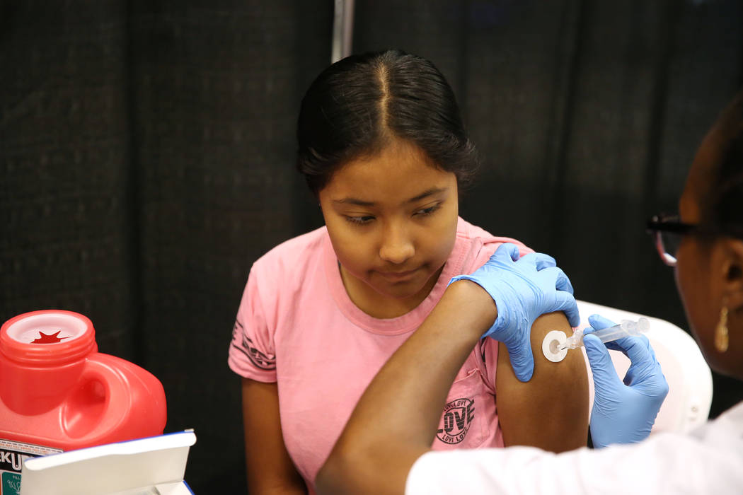 Lupita Rojas, 11, a seventh-grade-student from Las Vegas, receives a vaccine during the annual Cox Back to School Fair at Boulevard Mall in Las Vegas, Saturday, July 28, 2018. Erik Verduzco Las Ve ...