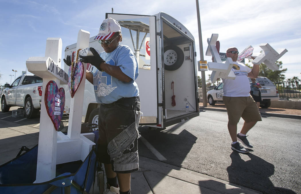 Las Vegas resident Debra Zellis, left, and Nick McKinley, visiting from Indiana, help carry the 58 crosses created by cross maker Greg Zanis to a spot near the Welcome to Fabulous Las Vegas sign h ...