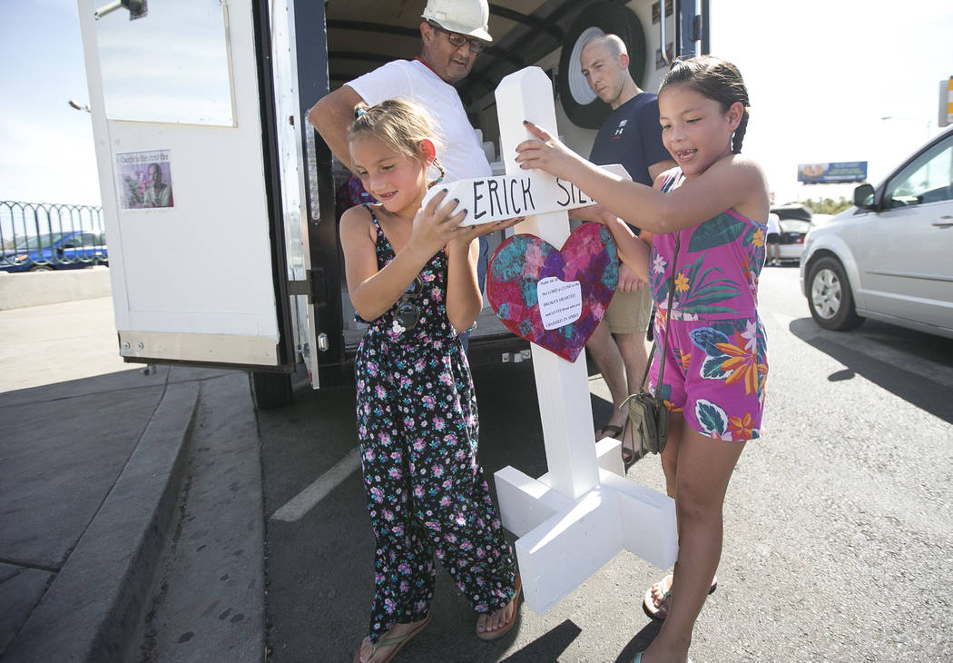 Tourists Emma Colon-Santiago, 8, left, and Lakynn Palos, 6, help carry one of 58 crosses created by cross maker Greg Zanis to a spot near the Welcome to Fabulous Las Vegas sign honoring victims of ...