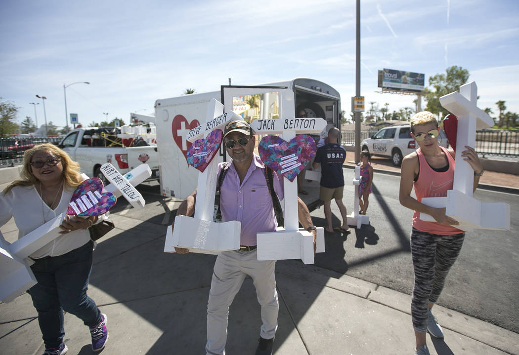 Several passersby help cross maker Greg Zanis unload 58 crosses to a spot near the Welcome to Fabulous Las Vegas sign honoring victims of the Oct.1 shooting on Friday, Sept. 28, 2018. Monday marks ...