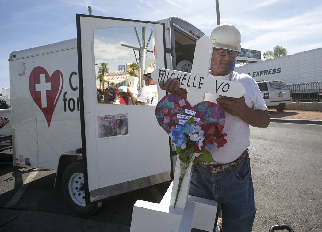 Greg Zanis, of Aurora, Ill., carries one of 58 crosses he placed near the Welcome to Fabulous Las Vegas sign honoring victims of the Oct.1 shooting on Friday, Sept. 28, 2018. Monday marks the one- ...
