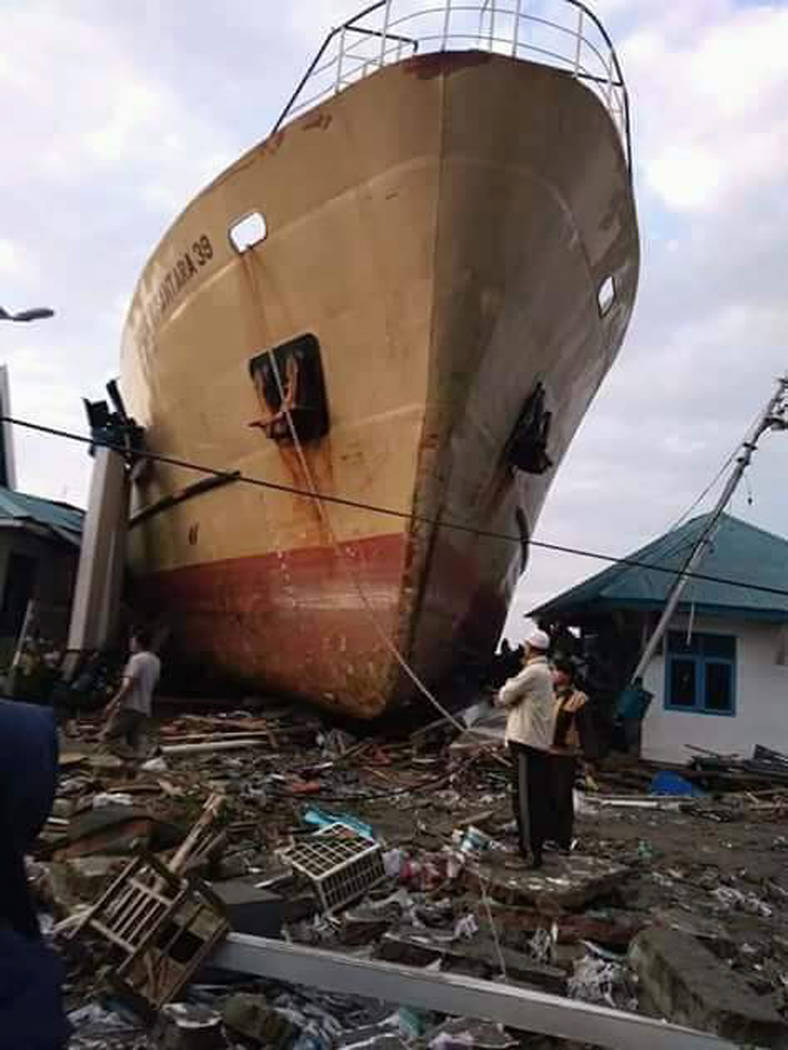 Villagers view a ship swept ashore by tsunami in Palu, Central Sulawesi, Indonesia, Saturday, Sept. 29, 2018. The powerful earthquake rocked the Indonesian island of Sulawesi on Friday, triggering ...
