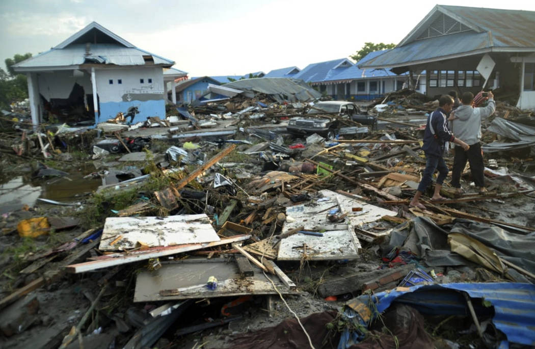 Indonesian men survey the damage following earthquakes and a tsunami in Palu, Central Sulawesi, Indonesia, Saturday, Sept. 29, 2018. A tsunami swept away buildings and killed large number of peopl ...