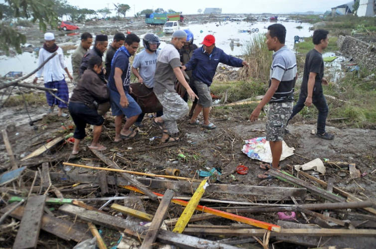 Residents carry a body bag containing the body of a tsunami victim in Palu, Central Sulawesi, Indonesia, Saturday, Sept. 29, 2018. (AP Photo)