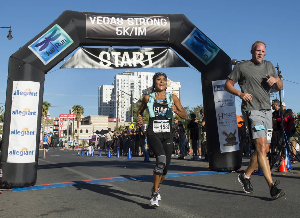 Gwynneth Hennis, left, and Jeff Moehling run across the finish line after participating in the Vegas Strong 5k/1-Mile, hosted by Jus Run, to commemorate the first anniversary of One October in Las ...