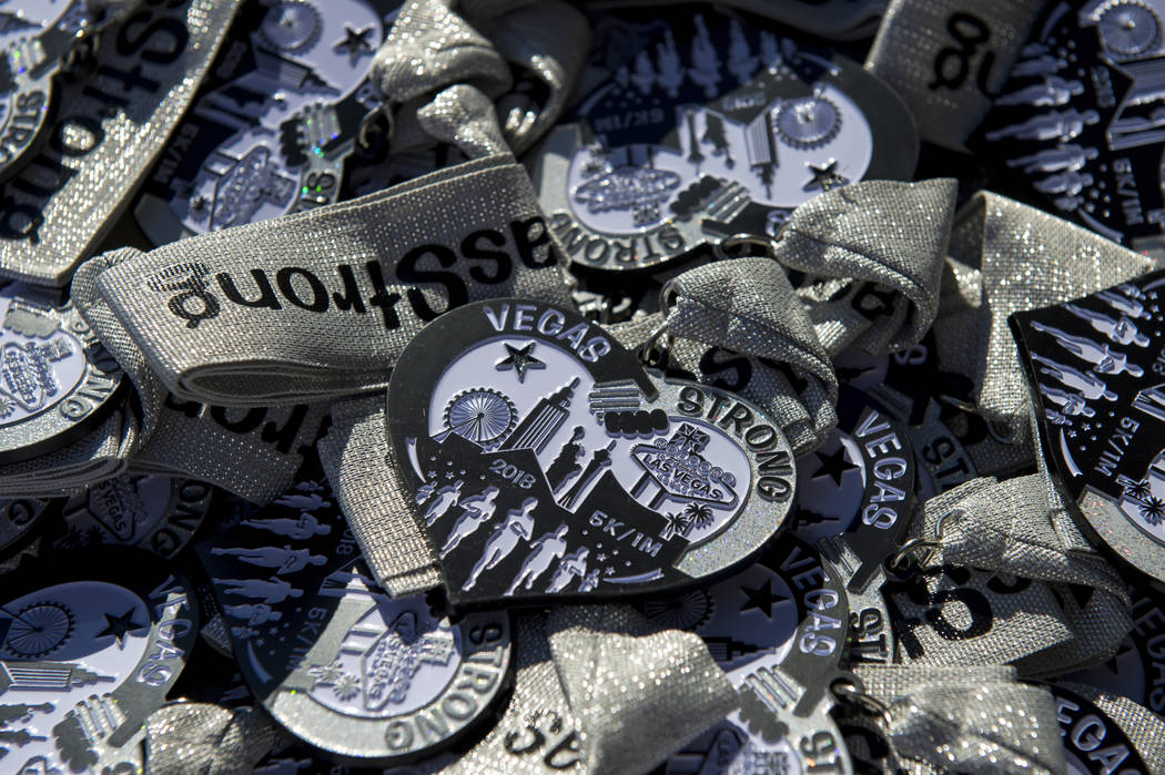 Participation medals are piled up on tables right next to the finish line for the runners of the Vegas Strong 5k/1-Mile, hosted by Jus Run, to commemorate the first anniversary of One October in L ...