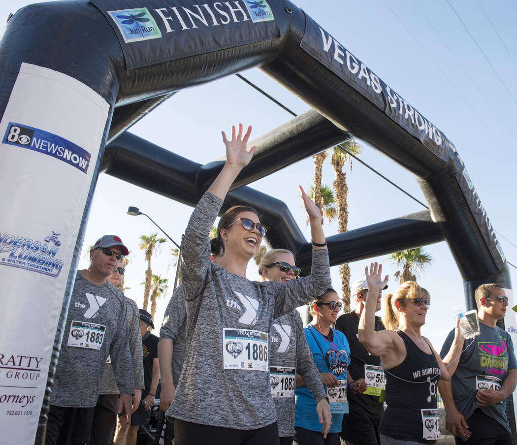 Sarah Neumann cheers as she walks across the start line at the Vegas Strong 5k/1-Mile, hosted by Jus Run, to commemorate the first anniversary of One October in Las Vegas, Sunday, Sept. 30, 2018. ...