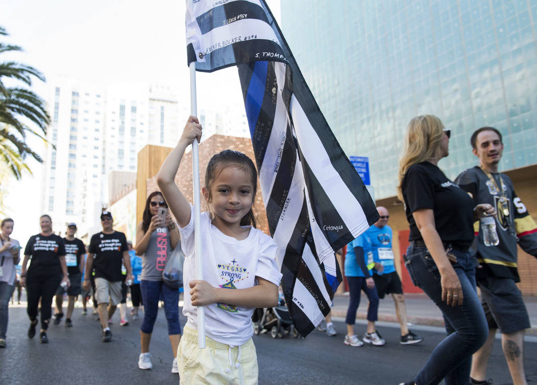 Theresa Babcock, 6, holds a flag to remember the police officers who lost their lives in the October One shooting as she walks in the Vegas Strong 5k/1-Mile, hosted by Jus Run, to commemorate the ...
