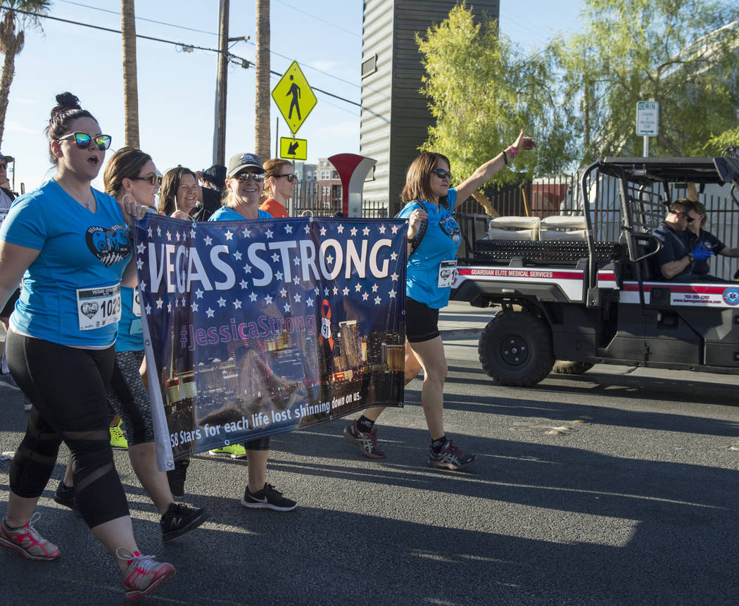 A group of women from Las Vegas hold up a flag to commemorate the October One shooting as they walking in the Vegas Strong 5k/1-Mile, hosted by Jus Run in Las Vegas, Sunday, Sept. 30, 2018. Caroli ...