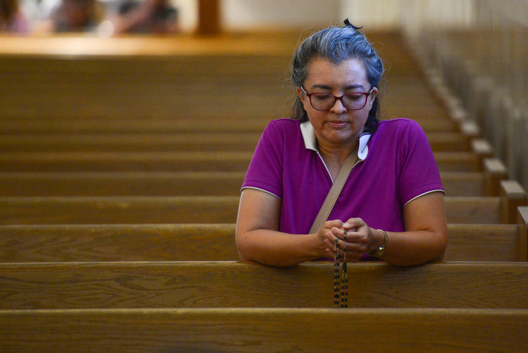 A woman who declined to give her name prays the Rosary before an interfaith service at Guardian Angel Cathedral in Las Vegas on Sunday, Sept. 30, 2018. The service, titled Dear Love: A Service of ...