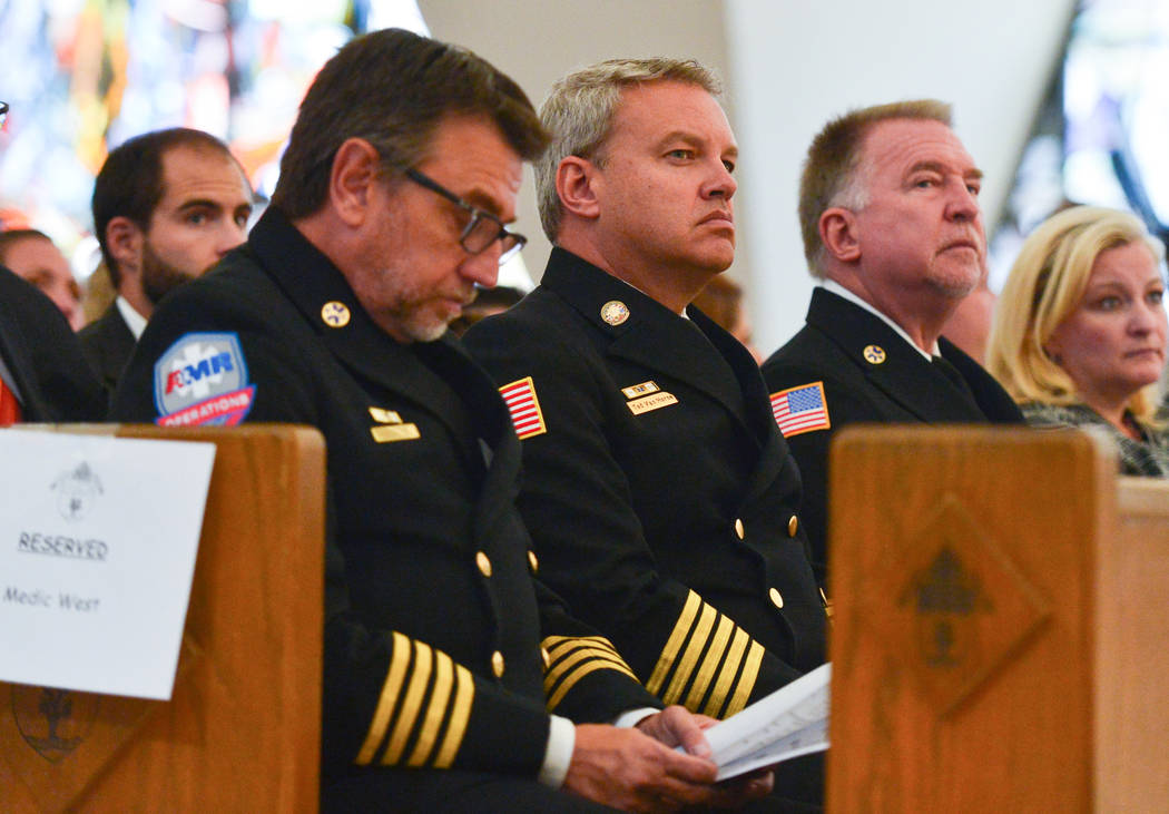 Ted Van Horne, center, of President of American Medical Response, listens to the choir at the beginning of an interfaith service at Guardian Angel Cathedral in Las Vegas on Sunday, Sept. 30, 2018. ...
