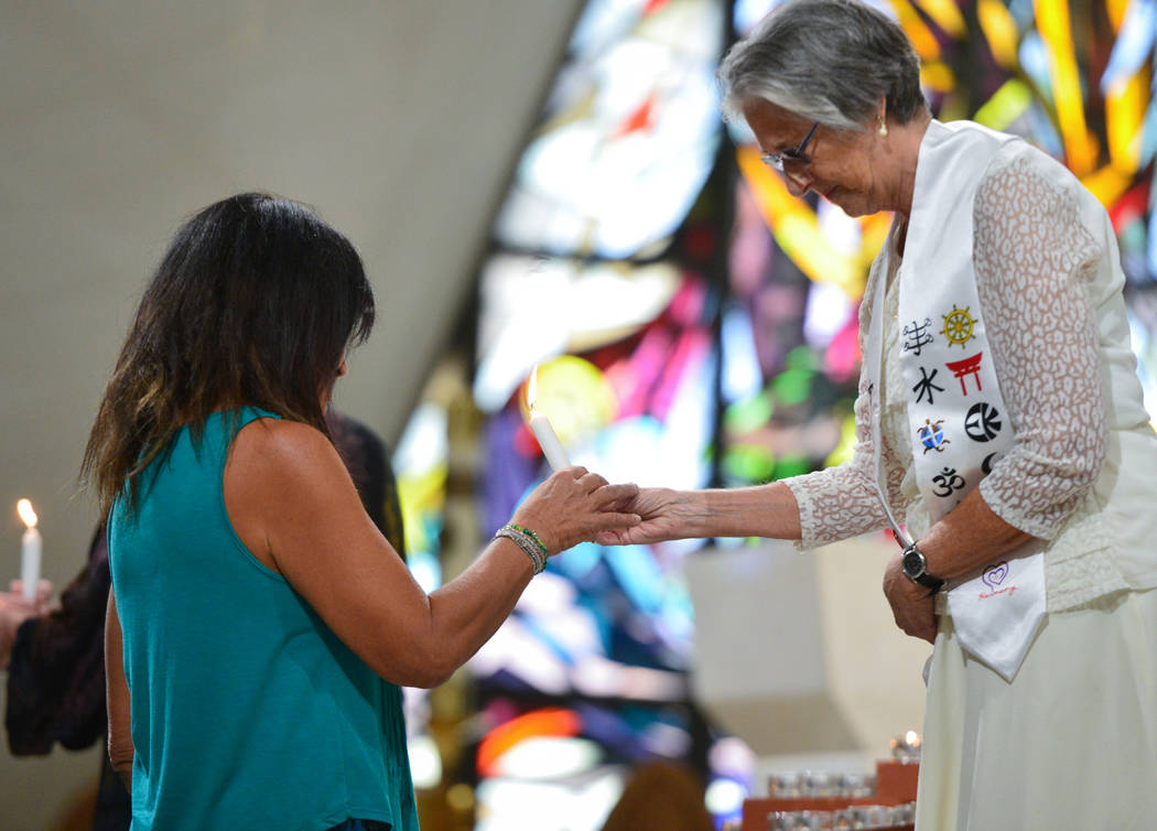 Interfaith service leaders hand off a candle at the beginning of an interfaith service at Guardian Angel Cathedral in Las Vegas on Sunday, Sept. 30, 2018. The service, titled Dear Love: A Service ...