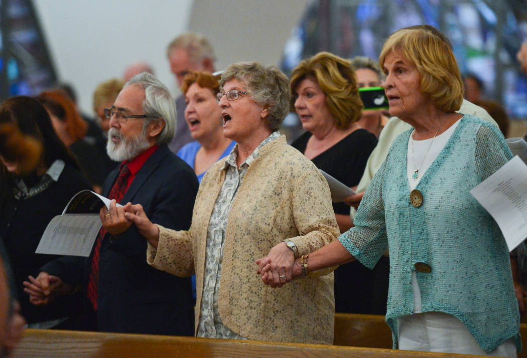 People join hands and sing during an interfaith service at Guardian Angel Cathedral in Las Vegas on Sunday, Sept. 30, 2018. The service, titled Dear Love: A Service of Hope, Healing, and Transform ...