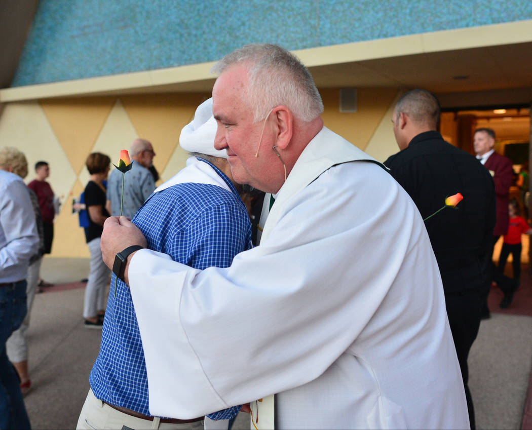 Teji Malik, left, who is on the board of directors for the Interfaith Council of Southern Nevada hugs Bob Stoeckig, right, Vicker General of the diocese of Las Vegas, after an interfaith service a ...