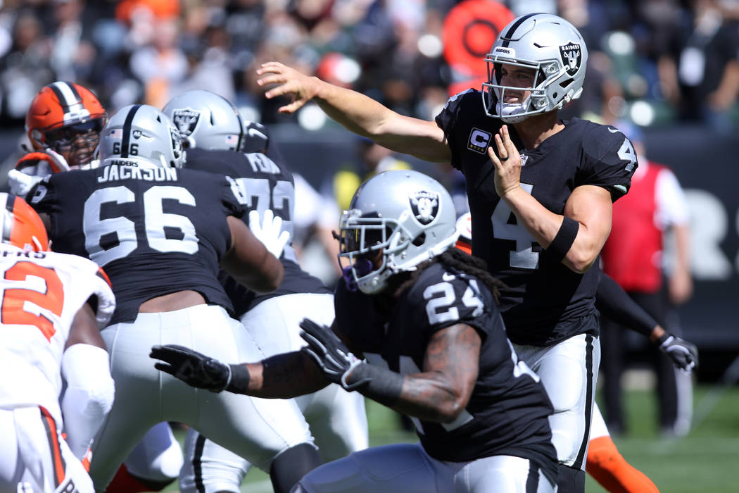 Oakland Raiders quarterback Derek Carr (4) throws the football as running back Marshawn Lynch (24) blocks for him during the first half of their NFL game against the Cleveland Browns in Oakland, C ...