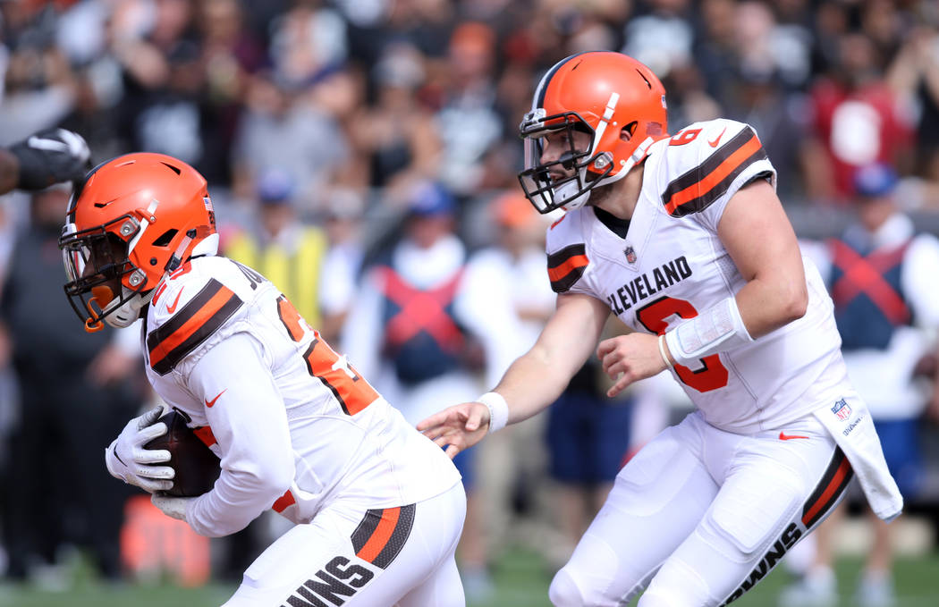 Cleveland Browns quarterback Baker Mayfield (6) hands off the football to running back Duke Johnson (29) during the first half of their NFL game against the Oakland Raiders in Oakland, Calif., Sun ...
