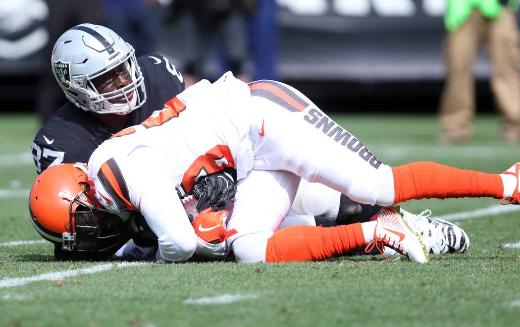 Oakland Raiders tight end Jared Cook (87) fights for the football as Cleveland Browns defensive back E.J. Gaines (28) intercepts quarterback Derek Carr (4), not pictured, during the first half of ...
