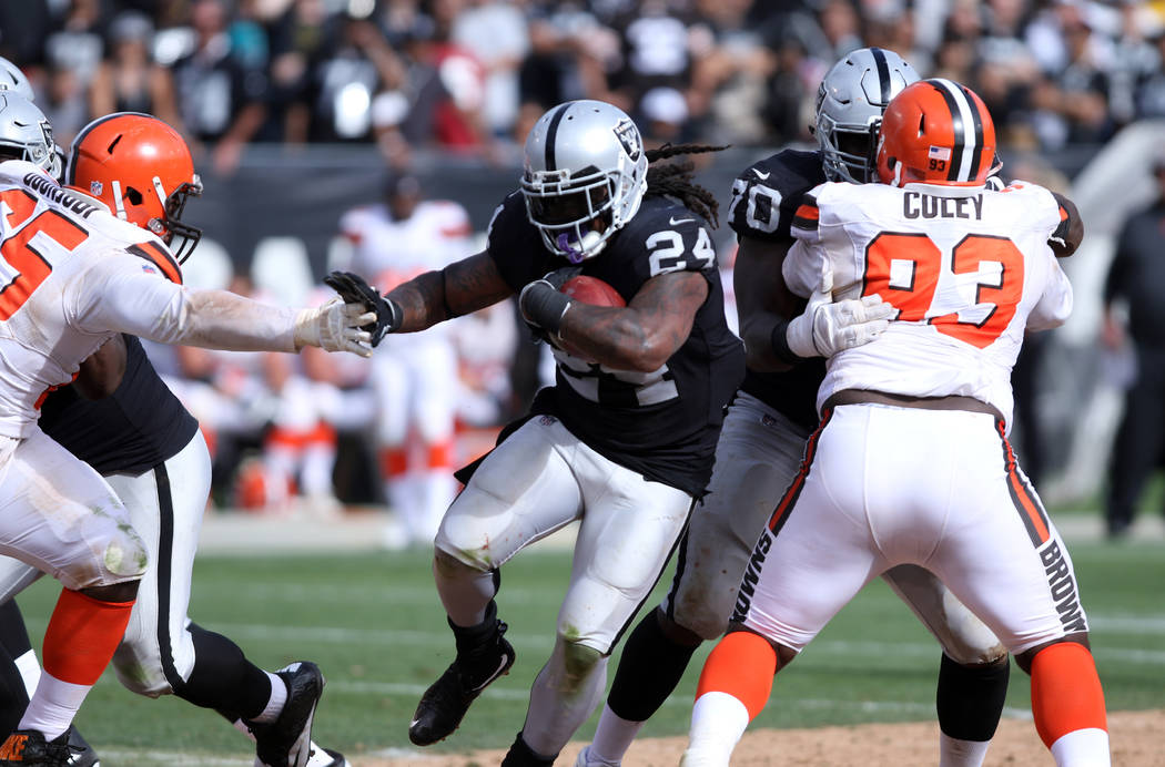 Oakland Raiders running back Marshawn Lynch (24) pushes away a hand from Cleveland Browns defensive tackle Larry Ogunjobi (65) as he looks for open field during the second half of their NFL game i ...