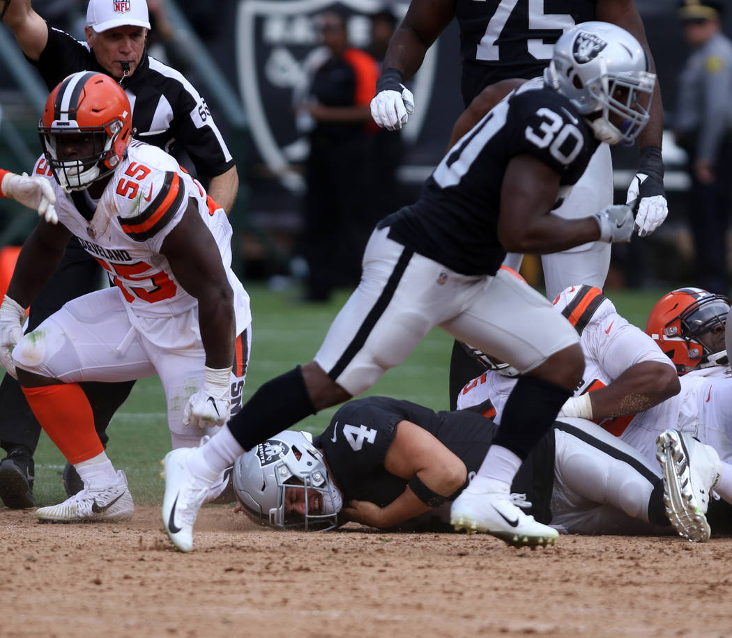 Oakland Raiders quarterback Derek Carr (4) grabs for his shoulder after being sacked by Cleveland Browns defensive end Myles Garrett (95) and linebacker Genard Avery (55) during the second half of ...