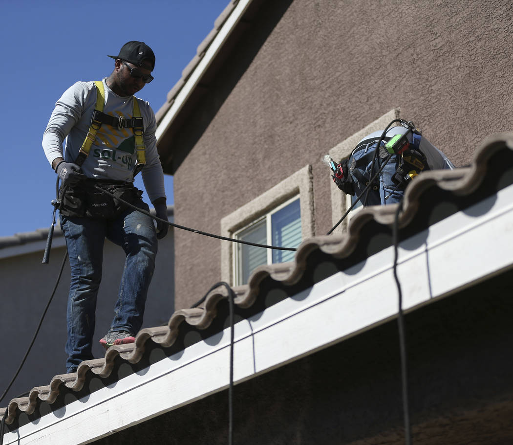 Brandon Lee, left, roof lead, and Brandon Lee, roof lead, prepare the roof for a residential solar panel installation in Henderson, Thursday, Oct. 18, 2018. Erik Verduzco Las Vegas Review-Journal ...