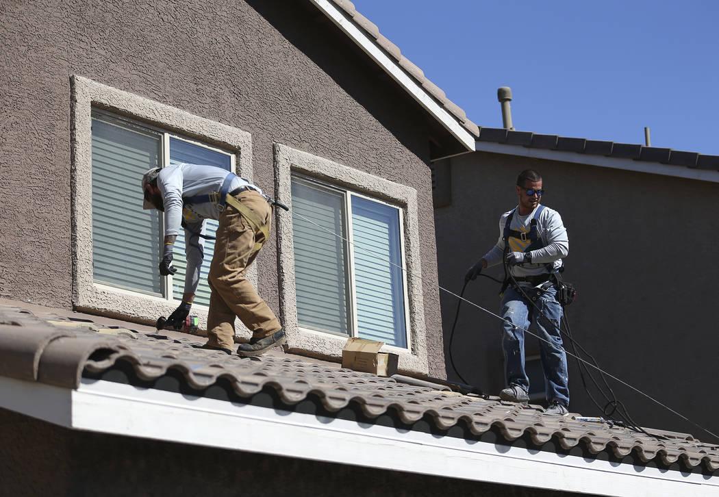 Sol-Up employees Zack Smith, left, general foreman, and Andrew Verdi, junior installer, prepare the roof for a residential solar panel installation in Henderson, Thursday, Oct. 18, 2018. Erik Verd ...