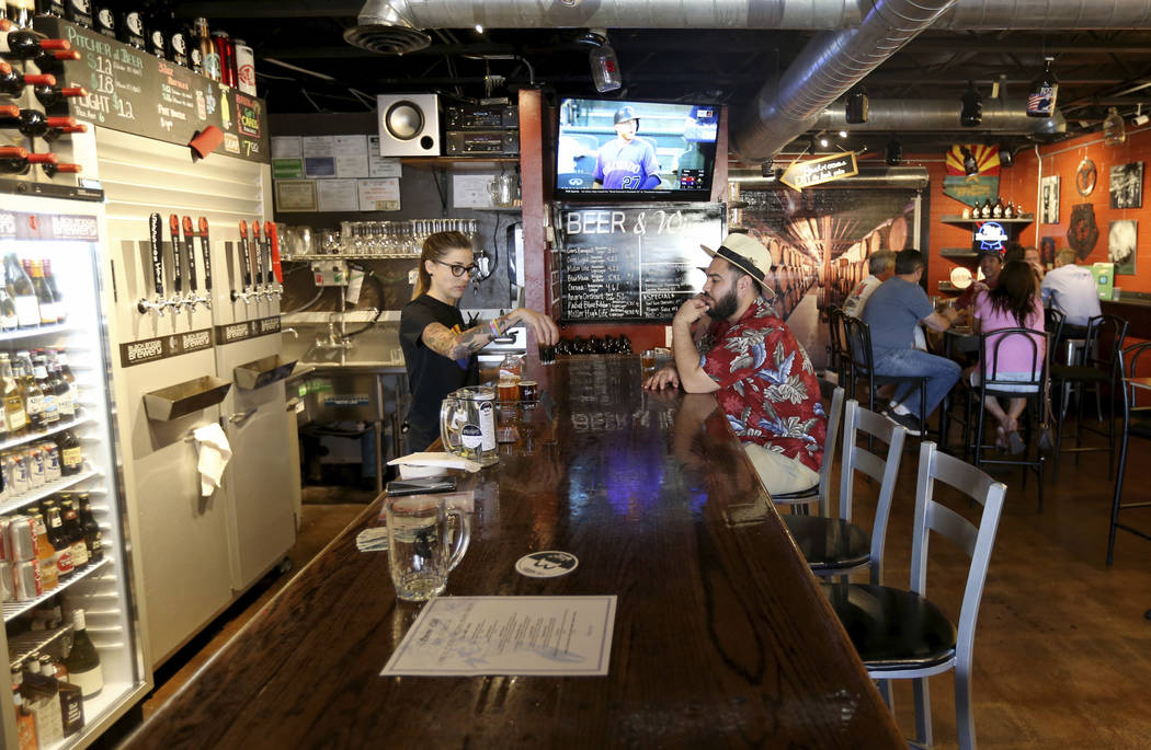 """Heather Howell serves beer at Black Bridge Brewery in Kingman, Ariz. Wednesday, Sept. 12, 2018. """"I like small towns and nice people, and we've got a lot of both right here."""" said Howell. ..."""