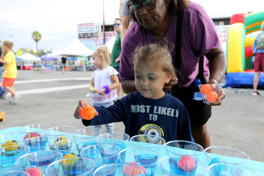 Prince Smith, 3, and grandmother Tina Smith play a game at 9th Bridge School 3rd annual Kidz Street STEAM-inspired block party presented by Zappos at The Lot at the Western in downtown Las Vegas S ...