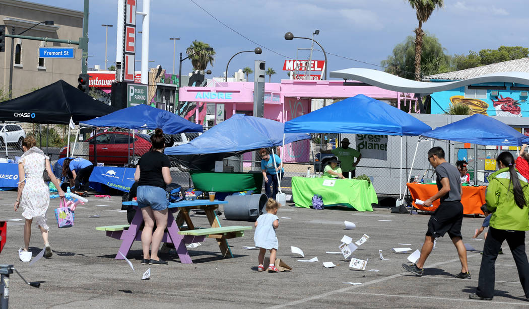People gather papers blown by high winds at 9th Bridge School 3rd annual Kidz Street STEAM-inspired block party presented by Zappos at The Lot at the Western in downtown Las Vegas Saturday, Oct. 6 ...