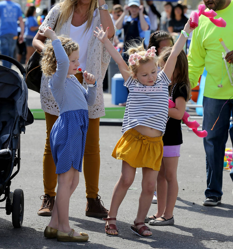 Scarlett Griffith, left, and Presley Paige, both 5, dance at 9th Bridge School 3rd annual Kidz Street STEAM-inspired block party presented by Zappos at The Lot at the Western in downtown Las Vegas ...