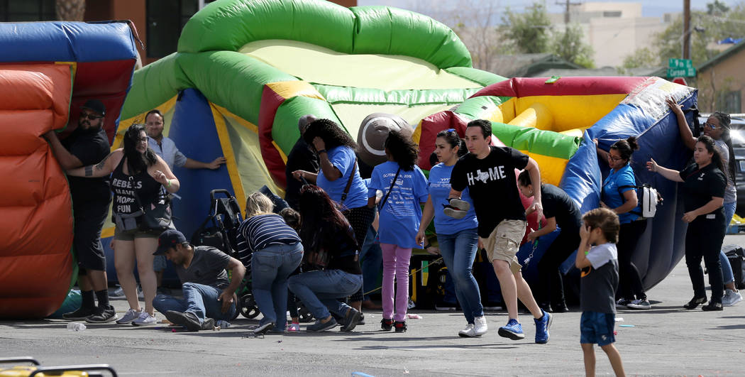 Bystanders help people after a bounce house became unsecured in high winds at 9th Bridge School's 3rd annual Kidz Street Festival presented by Zappos at The Lot at the Western in downtown Las Vega ...