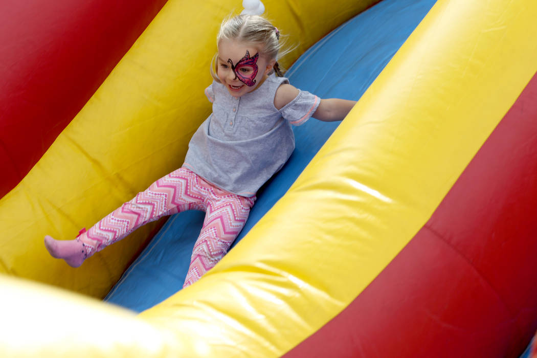 Haley Kelser, 3, rides an inflatable slide at 9th Bridge School 3rd annual Kidz Street STEAM-inspired block party presented by Zappos at The Lot at the Western in downtown Las Vegas Saturday, Oct. ...