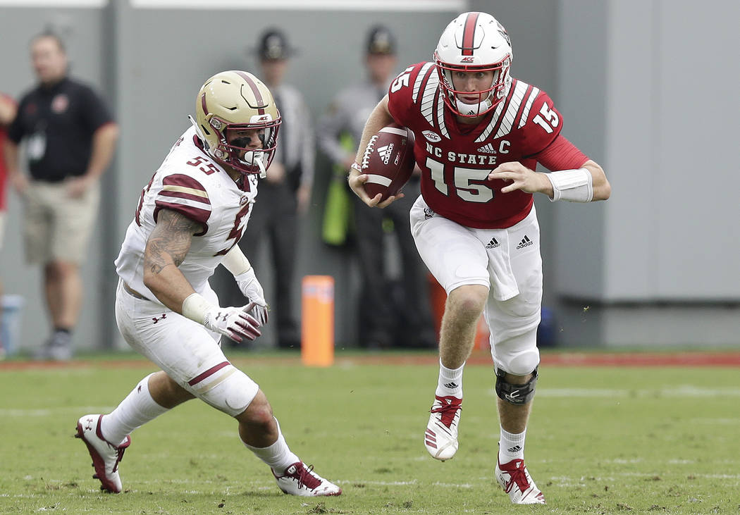 North Carolina State quarterback Ryan Finley (15) runs while Boston College's Isaiah McDuffie (55) misses the tackle during the first half an NCAA college football game in Raleigh, N.C., Saturday, ...