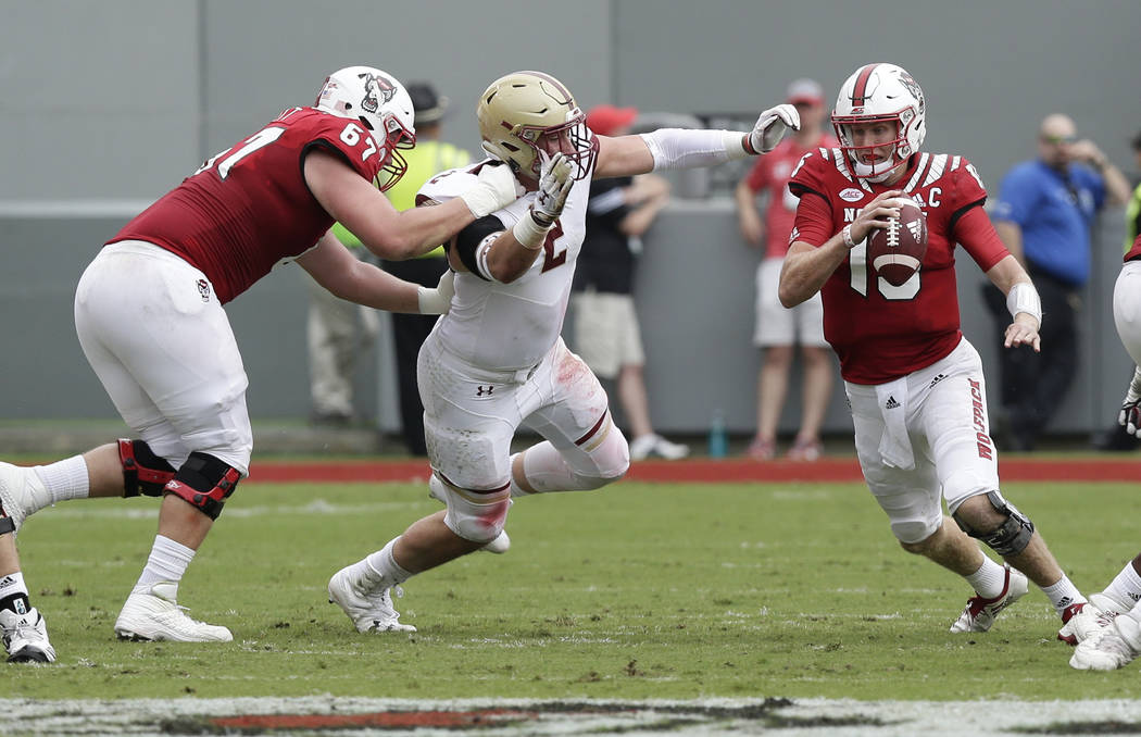 North Carolina State quarterback Ryan Finley (15) scrambles against Boston College's Zach Allen (2) during the first half an NCAA college football game in Raleigh, N.C., Saturday, Oct. 6, 2018. (A ...