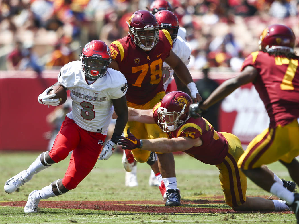 UNLV Rebels running back Charles Williams (8) runs the ball past USC Trojans linebacker Cameron Smith (35) during the first half of a football game at the Los Angeles Memorial Coliseum in Los Ange ...