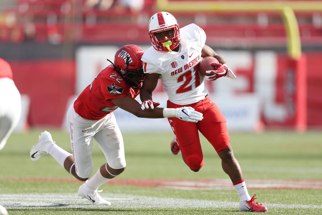 New Mexico Lobos running back Daevon Vigilant (21) runs the ball against UNLV Rebels defensive back Demitrious Gibbs (22) in the fourth quarter at Sam Boyd Stadium in Las Vegas, Saturday, Oct. 6, ...