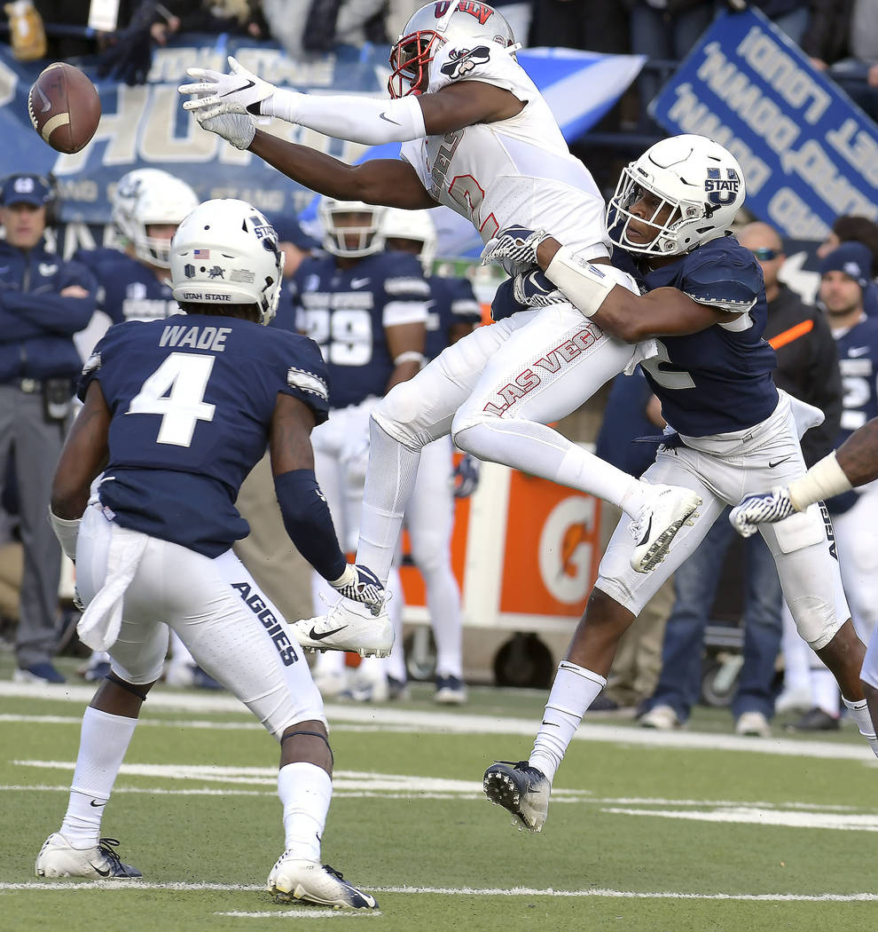 UNLV wide receiver Mekhi Stevenson (2) drops a pass as Utah State safety Aaron Wade (4) and cornerback Ja'Marcus Ingram defend during an NCAA college football game Saturday, Oct. 13, 2018, in Loga ...
