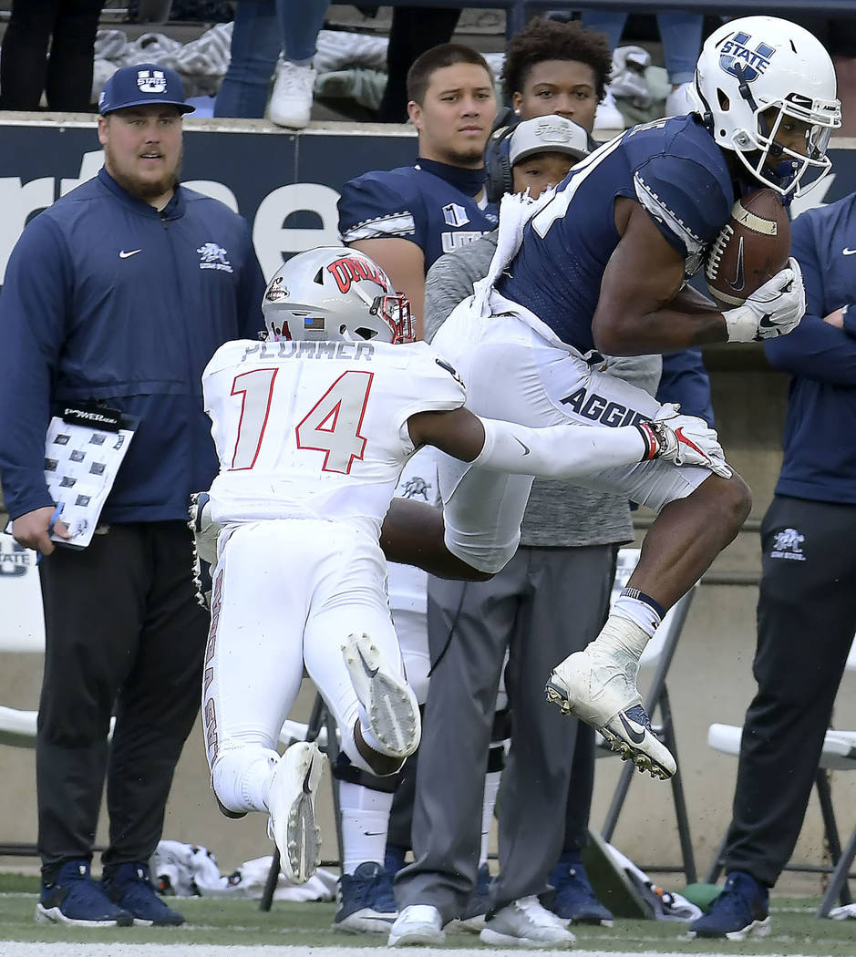 Utah State wide receiver Jalen Greene (21) catches a pass next to UNLV defensive back Myles Plummer during an NCAA college football game Saturday, Oct. 13, 2018, in Logan, Utah. (Eli Lucero/The He ...