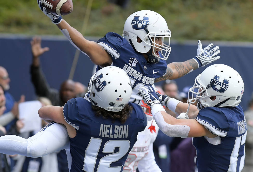 Utah State wide receiver Jordan Nathan (16) celebrates with teammates DJ Nelson (12) and Taylor Compton (17) after catching a 24-yard touchdown pass against UNLV during an NCAA college football ga ...