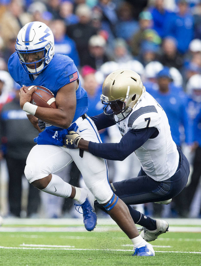 Air Force quarterback Isaiah Sanders (4) is brought down by Navy cornerback Khaylan Williams (7) during an NCAA college football game at Falcon Stadium at the U.S. Air Force Academy, Saturday Oct. ...