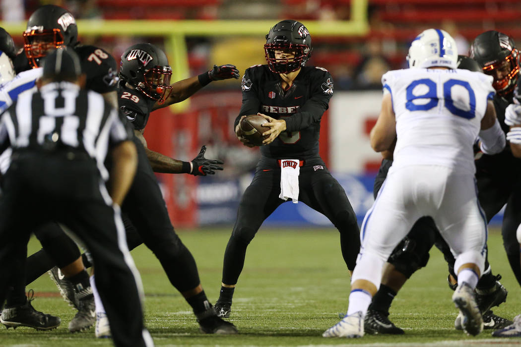 UNLV Rebels quarterback Max Gilliam (6), center, hands off the ball during the first quarter of the football game against Air Force Falcons at Sam Boyd Stadium in Las Vegas, Friday, Oct. 19, 2018. ...