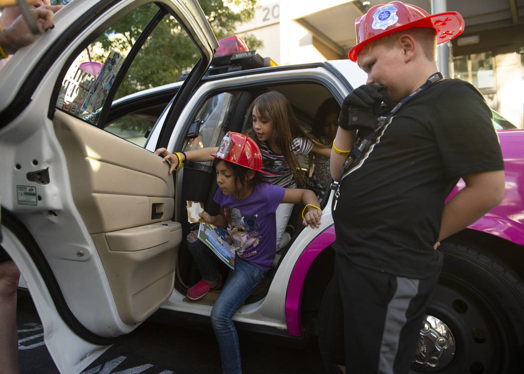 Maya Bible, 6, left, Isabella Bible, 8, make their way out of a police car as Andrew Harper, 8, watches at the LVMPD's National Night Out in the downtown Summerlin area of Las Vegas, Tuesday, Oct. ...