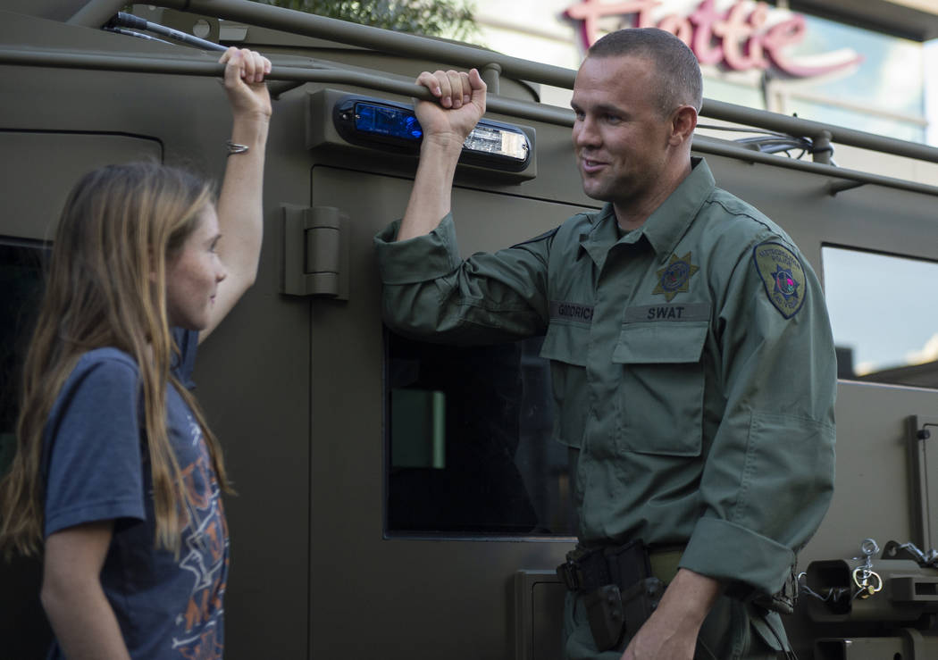 Ava Dupuis, 10, talks with Las Vegas SWAT officer Allyn Goodrich on the side of a SWAT vehicle at the LVMPD's National Night Out in the downtown Summerlin area of Las Vegas, Tuesday, Oct. 2, 2018. ...