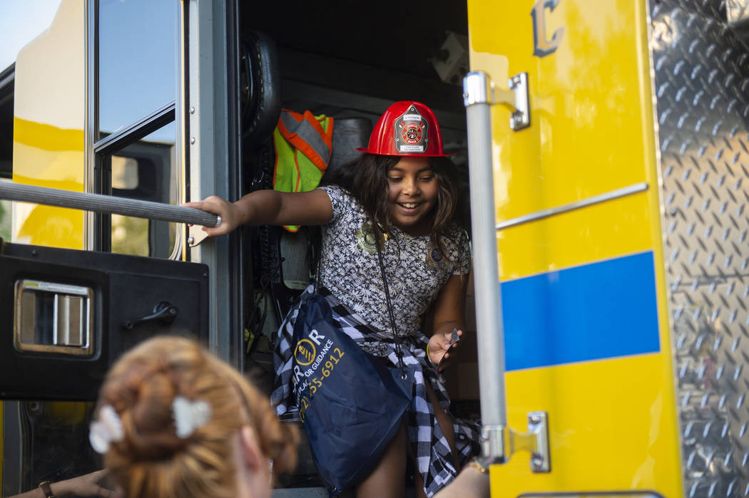 Alani Hernandez, 8, climbs out of a fire truck during the LVMPD's National Night Out in the downtown Summerlin area of Las Vegas, Tuesday, Oct. 2, 2018. Caroline Brehman/Las Vegas Review-Journal