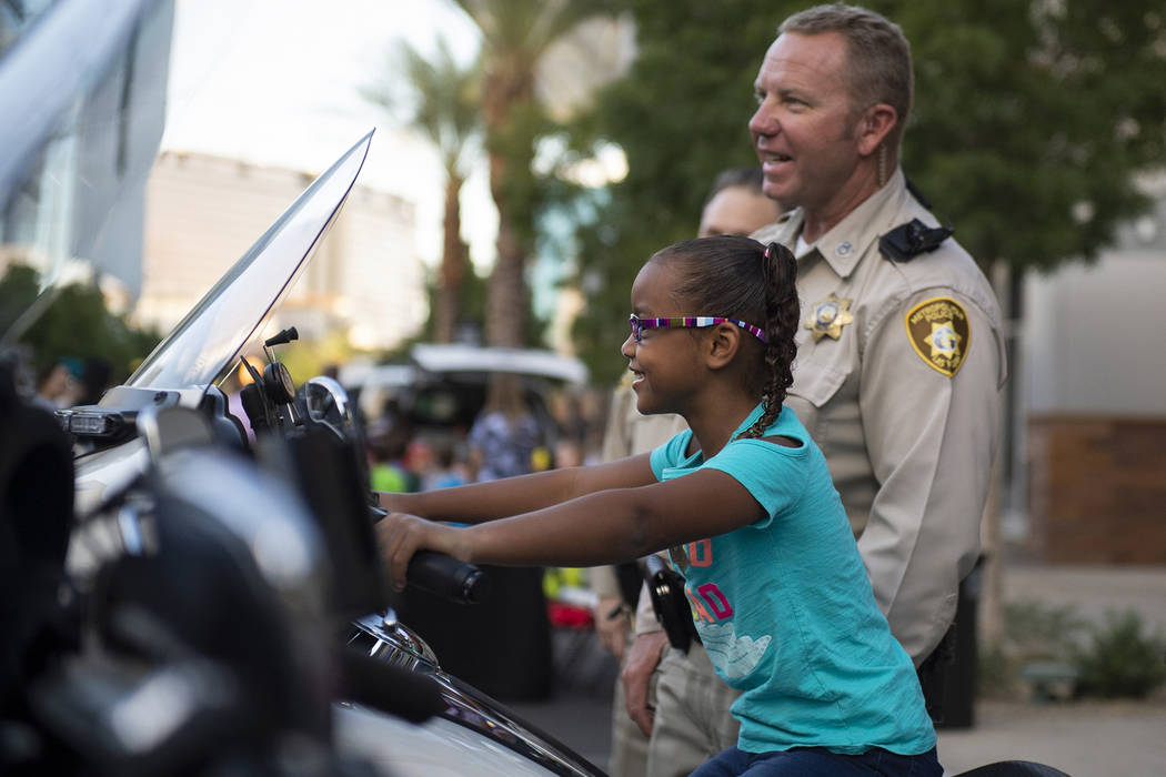 Riley English, 6, sits on top of a police motor cycle next to Las Vegas officer Michael Kendrick at the LVMPD's National Night Out in the downtown Summerlin area of Las Vegas, Tuesday, Oct. 2, 201 ...